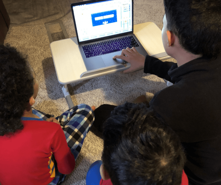 young boys reviewing a homeschool math program on a laptop